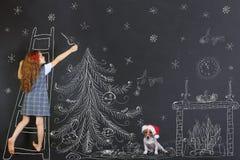 El niño y su perrito adorna un dibujo del árbol de navidad en blackb Fotografía de archivo libre de regalías
