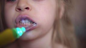 El ni?o cepilla sus dientes con un cepillo de dientes el?ctrico almacen de metraje de vídeo