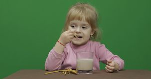 El ni?o come las galletas Una ni?a est? comiendo las galletas que se sientan en la tabla fotografía de archivo
