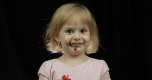 El ni?o con la cara sucia del chocolate derretido y de la crema azotada come la fresa foto de archivo