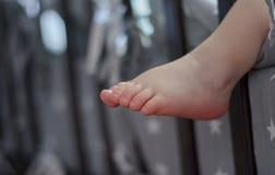 El ni?o est? durmiendo en cama, su pierna est? colgando abajo pierna de un peque?o beb? durmiente imagen de archivo