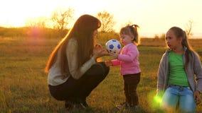 El ni?o feliz corre con la bola en hierba, lanza el bal?n de f?tbol Familia que juega con el peque?o ni?o por la bola de los ni?o almacen de video