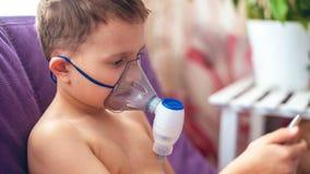 El ni?o hace el nebulizador de la inhalaci?n en casa en la cara llevar un nebulizador de la m?scara que inhalaba el vapor roci? l fotos de archivo