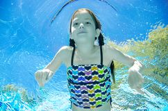 El ni?o nada bajo el agua en la piscina, zambullidas activas felices de la muchacha del adolescente y se divierte bajo el agua, l imagen de archivo