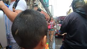 El ni?o peque?o est? caminando con festival del agua de la calle de Nana en Bangkok almacen de video