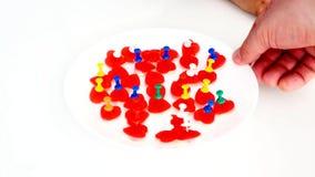 El ni?o peque?o perfora el caramelo en forma del coraz?n con los botones de los efectos de escritorio de colores brillantes metrajes