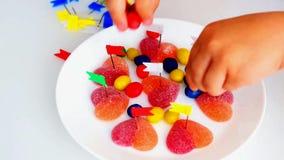 El ni?o peque?o perfora el caramelo en forma del coraz?n con los botones de los efectos de escritorio de colores brillantes almacen de metraje de vídeo