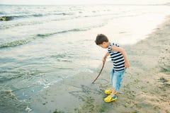 El ni?o peque?o por el mar lanza piedras en agua Puesta del sol Ni?ez feliz imágenes de archivo libres de regalías