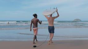 El Nido, Филиппины - 3-ье февраля 2019: Серфер молодого человека с доской прибоя идя к океану с тренером сток-видео