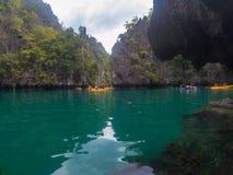 EL Nido, die Philippinen - 20. November 2018: Seelandschaft mit schwarzem Felsen und Touristen im Kajak Bootsausflug um Palawan lizenzfreie stockbilder