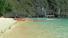 EL Nido, Filipinas - 1º de fevereiro de 2019: Bangka da canoa dos caiaque e do barco de Filipinas na praia tropical Oceano azul n video estoque