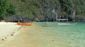 EL Nido, Filippine - 1° febbraio 2019: Bangka della canoa dei kajak e della barca di Filippine sulla spiaggia tropicale Oceano bl archivi video