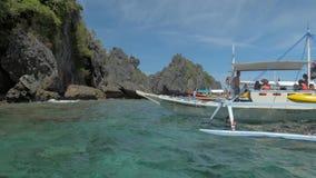 EL Nido, Filippine - 4 febbraio 2019: Barche filippine tradizionali di bangka ancorate sulla spiaggia tropicale splendida Corsa archivi video