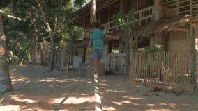 El Nido, Filippinerna - Februari 8, 2019: Ultrarapidskottet av den unga philippines pojken går tillbaka och jämvikt på arkivfilmer