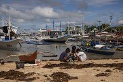 El Nido, Filippinerna - 22 November 2018: filippinobarn som spelar på sandstranden med fiskebåtar Etniskt folkarmod arkivbild