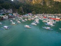 El Nido, Palawan, Philippines. Sunrise Light with Boats on Water. Pier in Background. El Nido, Palawan, Philippines. Sunrise Light Royalty Free Stock Photos
