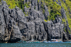 El Nido, Philippines - bancas in front of huge rocks. Bancas in front of huge rocks miniloc island. El Nido, Palawan, Philippines Royalty Free Stock Photography