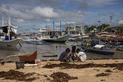 El Nido, Philippines - 22 Nov 2018: filippino children playing on sand beach with fishing boats. Ethnic people poverty stock photography