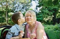 El nieto abraza y besa en la mejilla a su abuela rasgones adentro Imágenes de archivo libres de regalías