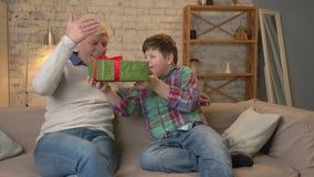 El nieto da a su abuelo un regalo un niño gordo da un regalo a un hombre mayor, alegría, sorpresa, felicidad, emoción metrajes