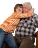 El nieto feliz abraza a un grandad feliz fotografía de archivo