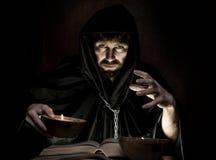 El nigromante echa encantos del libro antiguo grueso por luz de una vela en un fondo oscuro Imagen de archivo libre de regalías