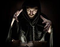 El nigromante echa encantos del libro antiguo grueso por luz de una vela en un fondo oscuro Fotos de archivo