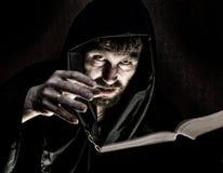 El nigromante echa encantos del libro antiguo grueso por luz de una vela en un fondo oscuro Fotografía de archivo