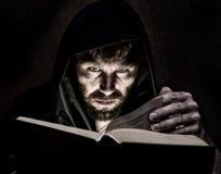 El nigromante echa encantos del libro antiguo grueso por luz de una vela en un fondo oscuro Imagenes de archivo