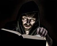El nigromante echa encantos del libro antiguo grueso por luz de una vela en un fondo oscuro Imagen de archivo