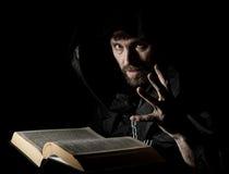 El nigromante echa encantos del libro antiguo grueso por luz de una vela en un fondo oscuro Imágenes de archivo libres de regalías