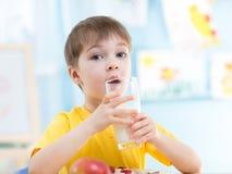 El niño bebe la leche sana en casa Imagenes de archivo