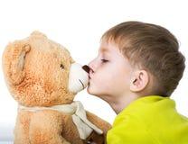 El niño besa el oso de peluche Imagen de archivo