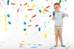 El niño de 3 años adorable del muchacho creativo mancha en la pared Foto de archivo