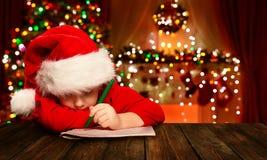 El niño de la Navidad escribe la letra Santa Claus, niño en la escritura del sombrero Imágenes de archivo libres de regalías