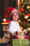 El niño dulce sonríe entre los regalos de la Navidad Imagen de archivo