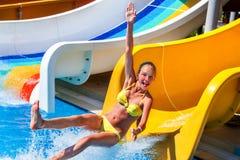 El niño en el tobogán acuático en la demostración del aquapark manosea con los dedos para arriba Imagen de archivo libre de regalías