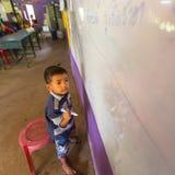 El niño en la lección en la escuela del camboyano del proyecto embroma cuidado Foto de archivo libre de regalías