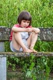 El niño enfocado que juega con la hiedra deja sentarse solamente en jardín Fotos de archivo