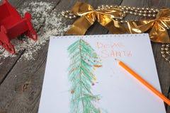 El niño escribe la letra a Papá Noel y dibuja un árbol de navidad Imágenes de archivo libres de regalías
