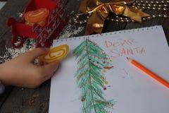 El niño escribe la letra a Papá Noel y dibuja un árbol de navidad Foto de archivo