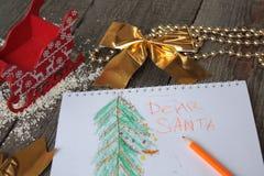 El niño escribe la letra a Papá Noel y dibuja un árbol de navidad Fotos de archivo