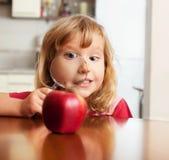 El niño está considerando una manzana de la lupa Fotos de archivo libres de regalías
