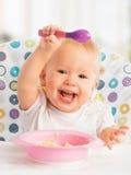 El niño feliz del bebé se come con una cuchara Imagen de archivo libre de regalías