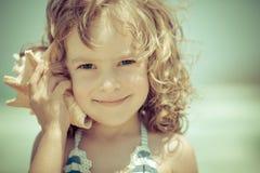 El niño feliz escucha la concha marina en la playa Imágenes de archivo libres de regalías