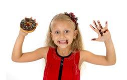 El niño femenino hermoso con los ojos azules en vestido rojo lindo que come el buñuelo del chocolate con el jarabe mancha Fotos de archivo