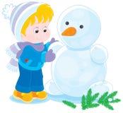 El niño hace un muñeco de nieve Imagen de archivo