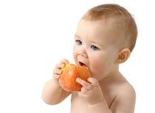 El niño hermoso come la manzana roja Fotografía de archivo libre de regalías