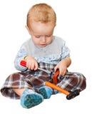 El niño juega con un destornillador del juguete, un martillo y los pequeños tornillos Foto de archivo