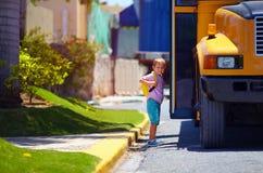 El niño lindo está consiguiendo en el autobús, alista para ir a la escuela Fotografía de archivo